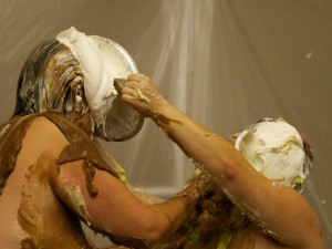 Mistress Messiér and Maya Kralovna exchange simultaneous pies at the Debauchery 2012 messyplay demo.